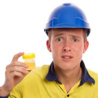 A young tradesman or apprentice with a suspect urine sample. Drug and alcohol testing on mine sites etc. Isolated on white.