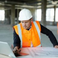 Portrait of development supervisor wearing protective vest and helmet over formal suit proofing blueprints using laptop computer inside unfinished building