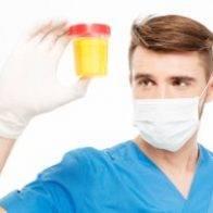 Male surgeon with mask holding bottle of urine sample isolated on white background